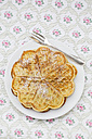 Dish of waffles sprinkled with icing sugar on patterned cloth - LVF002374