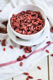 Bowl of Goji berries, Lycium barbarum, on kitchen towel and wood - SBDF001507