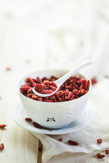 Bowl of Goji berries, Lycium barbarum, on kitchen towel and wood - SBDF001508