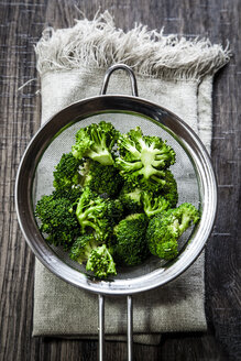 Colander of broccoli florets on cloth and wood - SARF001087