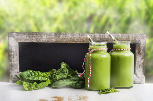 Two glasses of spinach smoothie, spinach leaves and blackboard - ODF000899