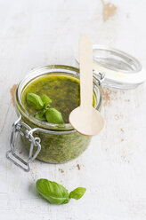 Preserving jar of fresh pesto, wooden spoon and basil leaves on white wood - ODF000902