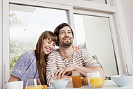 Happy couple at home having breakfast - FMKF001369