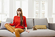 Serious woman sitting on sofa next to cuddly toy - FMKF001432