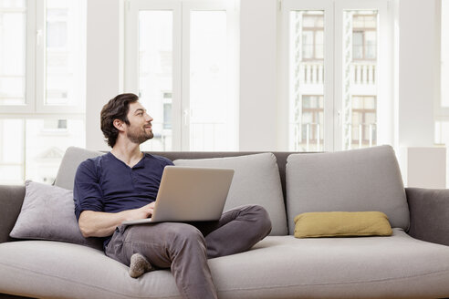 Man sitting on couch using laptop - FMKF001388
