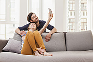 Happy couple taking selfie at home - FMKF001433