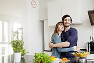 Happy couple embracing in kitchen - FMKF001403