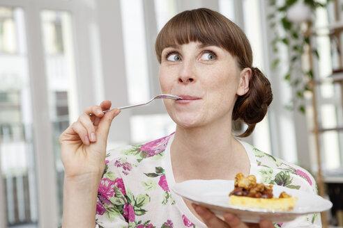 Smiling woman enjoying piece of cake - FMKF001408