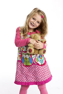 Portrait of happy litlle girl with her teddy-bear wearing colourful dress in front of white background - GDF000618