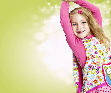 Portrait of smiling girl with outstretched arms in front of light green background - GDF000630