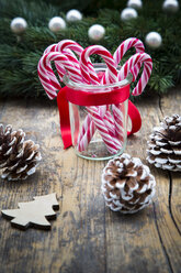 Glass of sugar canes and fir cones on wood - LVF002393