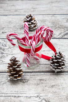 Glass of sugar canes and fir cones on wood - LVF002396