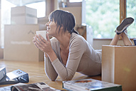Woman having a coffee break during moving house - ZEF002838
