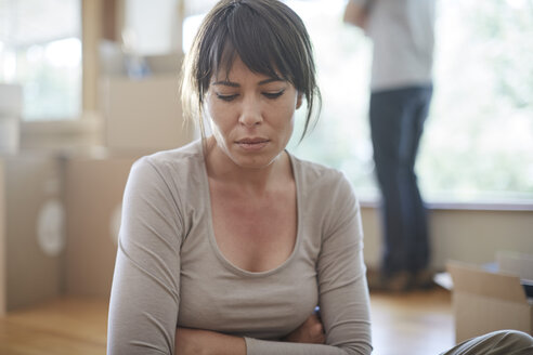 Woman sitting and feeling unhappy during moving house - ZEF002841