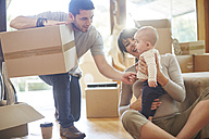 Family moving house sitting with a baby - ZEF002843