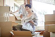 Couple moving house unpacking glasses - ZEF002850