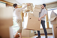 Couple moving house stacking boxes - ZEF002853