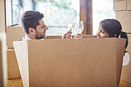 Couple moving house sitting in a box and clinking wine glasses - ZEF002859