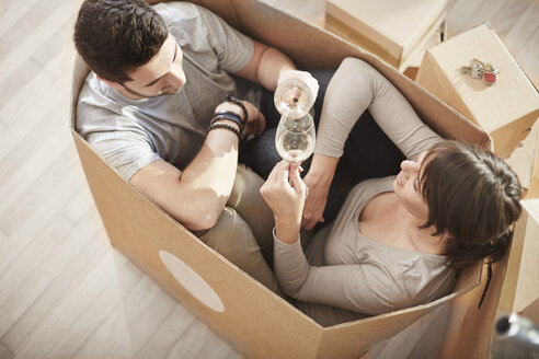 Couple moving house sitting in a box and clinking wine glasses - ZEF002861
