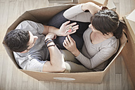 Couple moving house sitting in a box and holding key - ZEF002862