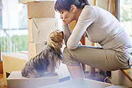 Woman moving house sharing a moment with the dog - ZEF002911