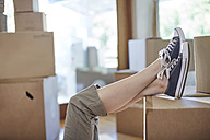 Couple moving house, woman's feet on a box - ZEF002867