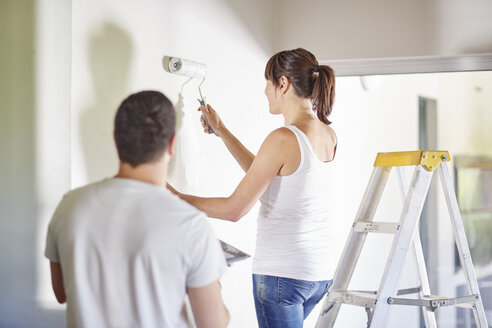 Couple painting the wall in new home - ZEF002872