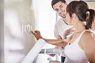 Couple painting heart at the wall in new home - ZEF002875