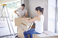 Couple moving house, woman writing on box - ZEF002879
