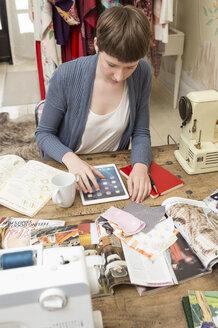 Female fashion designer using digital tablet at her work desk - DISF001119