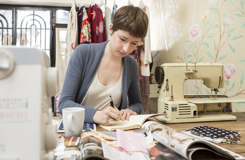 Female fashion designer drawing at her work desk - DISF001126