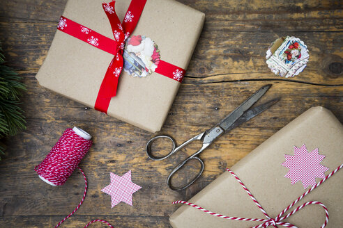 Wrapped Christmas presents and scissors  on dark wood - LVF002407