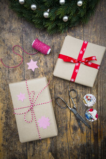 Wrapped Christmas presents and scissors on dark wood - LVF002405