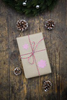Wrapped Christmas present and fir cones on dark wood - LVF002404