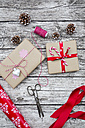 Wrapped Christmas presents, fir cones, ribbon and scissors on wood - LVF002402