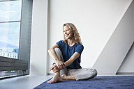 Portrait of happy mature woman sitting on carpet at home looking through window - RBF002056