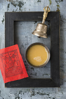 Bowl of butter tea, red prayer flag, black picture frame and bell on grey ground - MYF000726