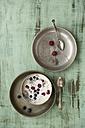 Metal bowl of vanilla yoghurt with chia, Salvia hispanica, blueberries and raspberries on green wood - MYF000731