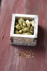 Little box of cardamom capsules on wood - MYF000744