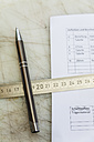 Metal ruler and pen on construction spreadsheet - TCF004377