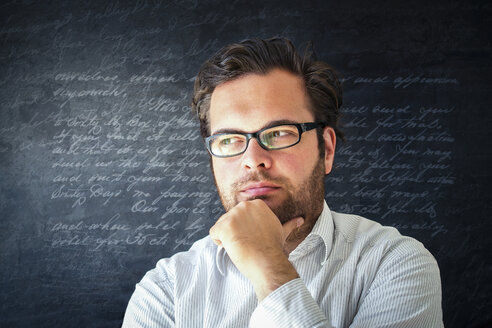 Portrait of pensive man with full beard wearing glasses in front of dark background with writings - PUF000352