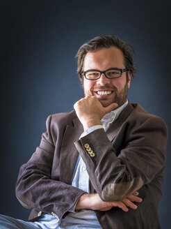 Portrait of smiling man with full beard wearing glasses in front of dark background - PUF000354