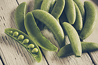 Whole and opened peasecods of snow peas on wood - SARF001121