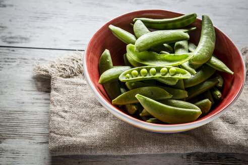 Bowl of whole and opened peasecods of snow peas on cloth and wood - SARF001124