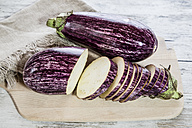 Whole and sliced organic aubergines on kitchen board - SARF001130