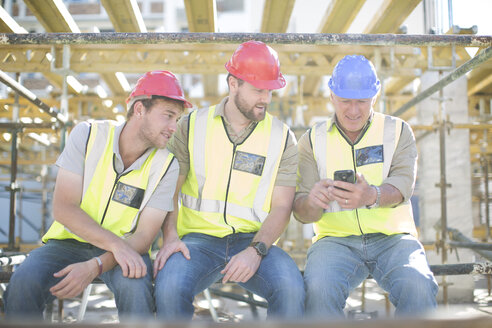 Construction workers with cell phone having a break - ZEF001622