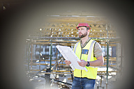 Construction worker holding plan at construction site - ZEF001638