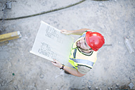 Construction worker holding plan at construction site - ZEF001650