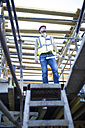 Construction worker looking at top of staircase - ZEF001957
