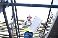 Construction worker reading plan at construction site - ZEF001656